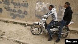 Des chômeurs assis sur une moto dans le quartier pauvre de Zhor, à Kasserine. Sur le mur, on peut lire un graffiti «Jeunes marginaux».