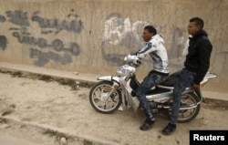 "Unemployed men sit on motorcycle beside a graffiti which reads ""Marginalized youth"" at the impoverished Zhor neighborhood of Kasserine, where young people have been demonstrating for jobs since last week, Jan. 28, 2016."