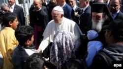 Le pape François, au centre, salue les enfants réfugiés à son arrivée au camp de ces derniers à Moria, sur l' île de Lesbos, Grèce, 16 avril 2016. epa/ ORESTIS