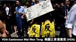 化名Blue的香港市民帶同一對年幼子女參與黑衣遊行,她認為公義比經濟增長重要。(攝影: 美國之音湯惠芸)