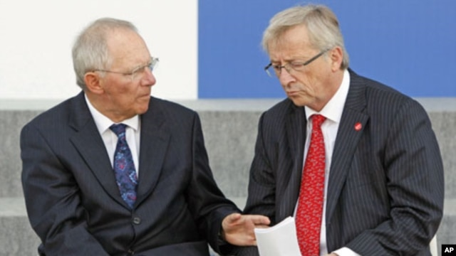 Germany Finance Minister Wolfgang Schauble (L) talks to Eurogroup President Jean-Claude Juncker after posing with other European Union finance ministers for a photo during a meeting of the Economic and Financial Affairs Council in Wroclaw, Poland, Septemb