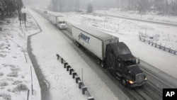 Amid powerful storms bringing snow and rain, vehicles make their way along eastbound Interstate 80 near Soda Springs, California, Dec. 11, 2014.