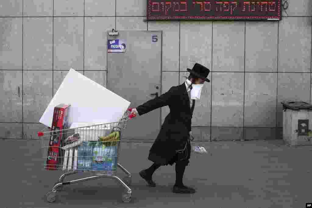 ជនជាតិជ្វីស គោរពតាមការប្រតិបត្តិសាសនាគ្រិស្តultra-Orthodox ពាក់ម៉ាសកែច្នៃ នៅពេលគាត់ទាញរទេះរុញនៅលើផ្លូវក្បែរផ្សារមួយដែលគ្មានមនុស្ស ដោយសារតែវិធានការរបស់រដ្ឋាភិបាលក្នុងការទប់ស្កាត់ការរីករាលដាលនៃវីរុសកូរ៉ូណា នៅទីក្រុងBnei Brak នៅជាយក្រុង Tel Aviv ប្រទេសអ៊ីស្រាអែល។