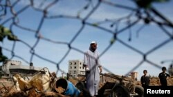FILE - A Palestinian man inspects the scene of an Israeli air strike in the central Gaza Strip, Apr. 21, 2014.