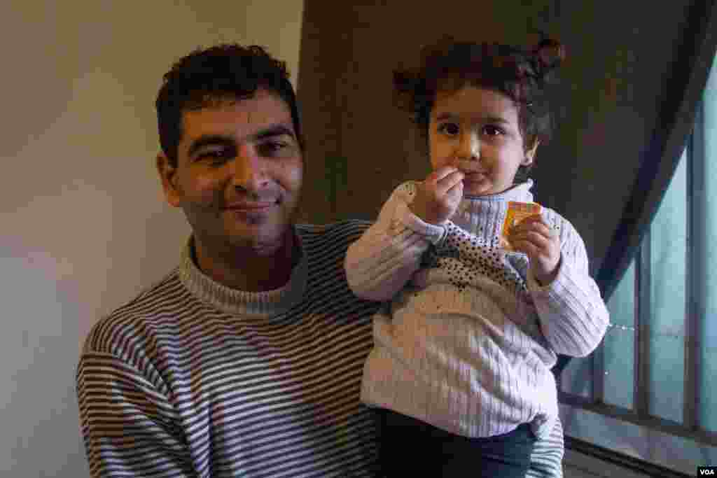 Ahmad with his daughter Ritaj, 2. Ahmad fears that his children will not get an education, John Owens/VOA.