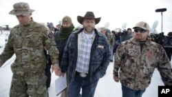 FILE - Ammon Bundy, center, walks off after speaking with reporters during a news conference at Malheur National Wildlife Refuge headquarters Jan. 4, 2016, near Burns, Oregon.