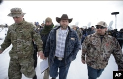 FILE - Ammon Bundy, center, one of the sons of Nevada rancher Cliven Bundy, walks off after speaking with reporters during a news conference at Malheur National Wildlife Refuge headquarters Jan. 4, 2016, near Burns, Ore.