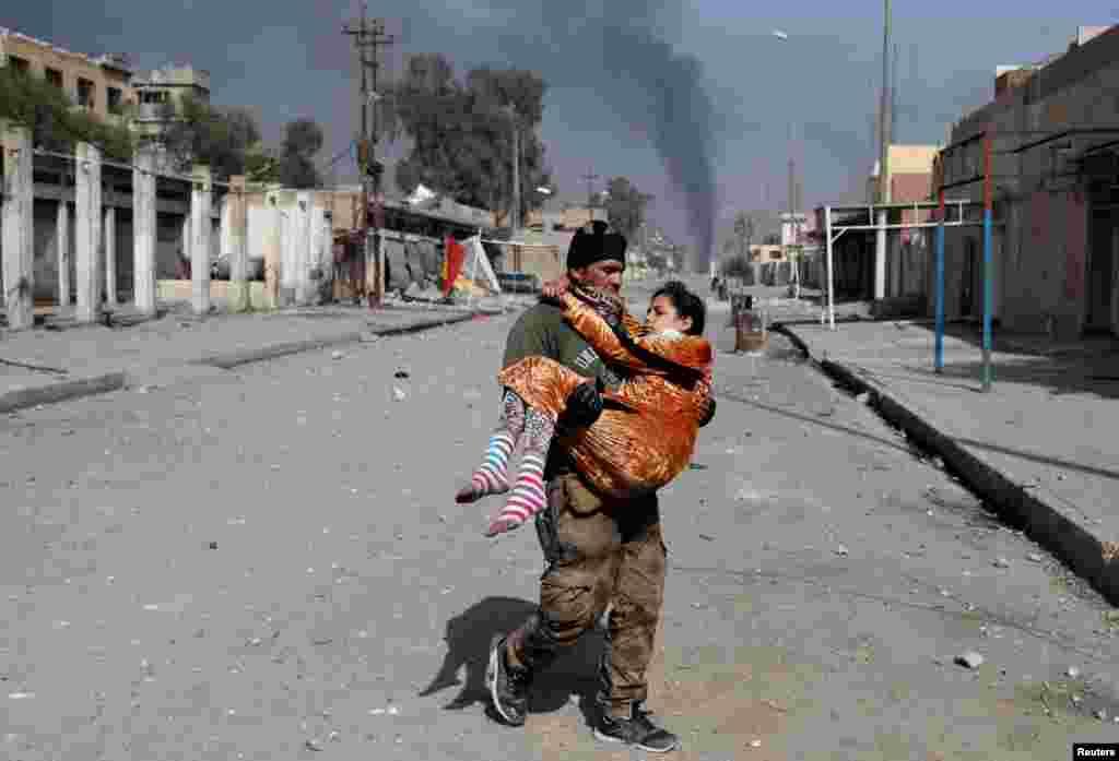 یک سرباز عراقی به یک زنی که در نبرد بین نیروهای عراقی و داعش در موصل زخمی شده، کمک میکند.