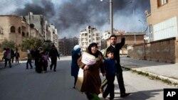 Một gia đình bỏ chạy khỏi các vụ giao tranh ác liệt giữa Lực lượng Quân đội Giải phóng Syria và quân đội chính phủ Syria tại Idlib, phía bắc Syria, ngày 10/3/2012