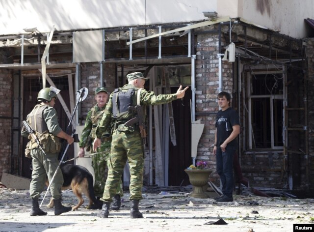 FILE - A serviceman directs a pedestrian away from the scene of a suicide bomb attack in Grozny, the capital of Russia's Chechnya region, Aug. 31, 2011.