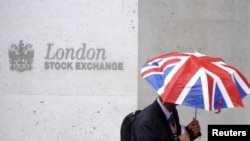 FILE - A worker shelters from the rain as he passes the London Stock Exchange in the City of London at lunchtime, Oct. 1, 2008.