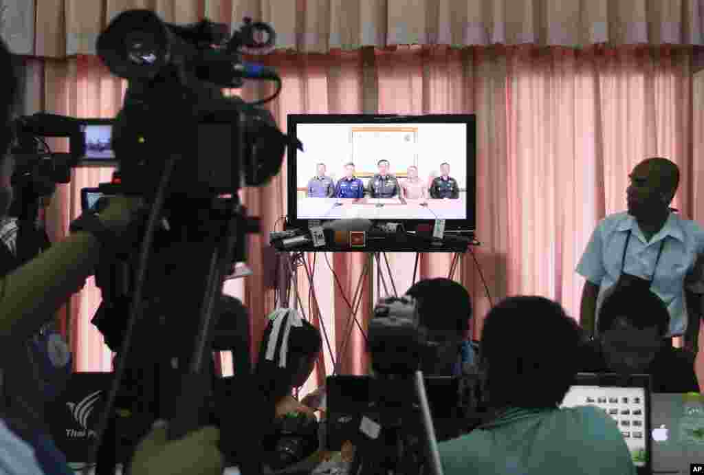 Thai journalists and other foreign press watch the TV broadcast announcement of the coup by the Thai Armed Forces chiefs, at the press center of the Army Club, in Bangkok, May 22, 2014.