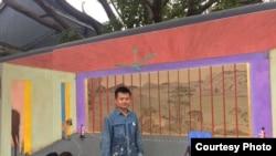 """畫家胡嘉岷和他的壁畫《時差》(圖片來源﹕""""自由劉曉波工作組""""推特帳號)"""