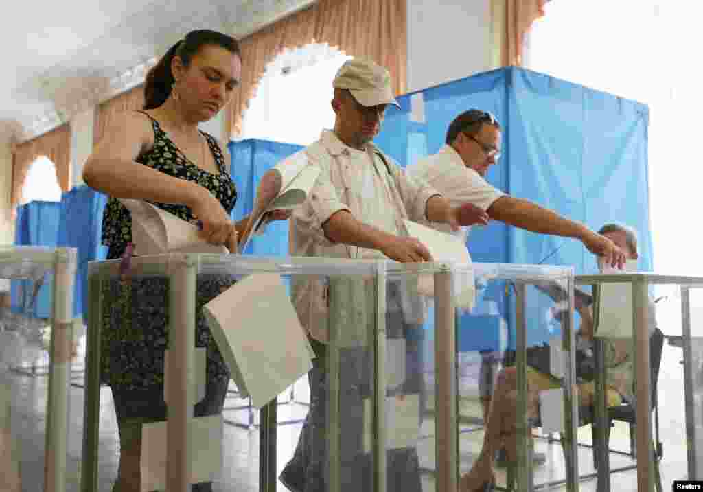 People cast their ballots during voting in a presidential election at polling station in Kyiv.