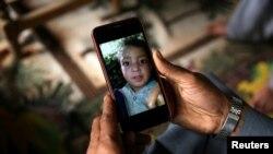 Seorang kerabat memperlihatkan foto Mohammad Ayan Ali, 4 tahun, yang menurut keluarganya, tewas setelah memainkan alat yang mirip mainan dan meledak di tangannya di rumahnya, Desa Jabri, Lembah Neelum, wilayah Kashmir yang dikontrol Pakistan, 9 Agustus 2019. (Foto: Reuters)