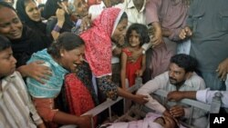 Pakistani family members mourn the death of a man shot dead amid unabated violence in Karachi, Pakistan, July, 8, 2011.