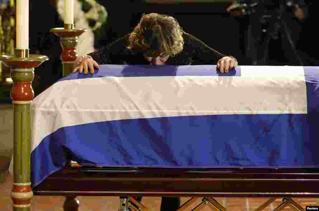 Renata Ford, the widow of former Toronto mayor Rob Ford who died last week of cancer, kisses his coffin during his funeral at St. James Cathedral in Toronto, Canada.