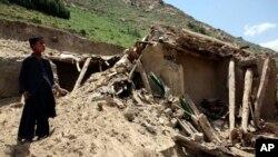 Seorang anak tengah berdiri di depan sebuah rumah yang hancur terkena gempa di Baghlan, utara Kabul, Afghanistan (26/10).