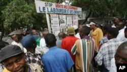 Quelques passants lisent les titres des journaux étalés sur une place publique à Kinshasa, RDC, 29 juillet 2006.