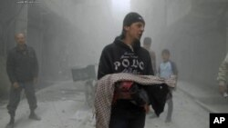 This photo provided by the anti-government activist group Aleppo Media Center (AMC), which has been authenticated based on its contents and other AP reporting, shows a Syrian man carrying the body of a child killed by a government forces airstrike in the