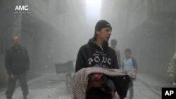 一名叙利亚男子举着一个在叙利亚政府军的空袭中丧生的婴儿的遗体