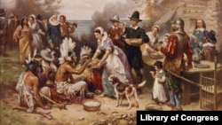 FILE - A painting by Jean Leon Gerome Ferris titled 'The First Thanksgiving' shows pilgrims and Native Americans gathering to share a meal.