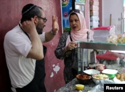 A Tunisian Muslim woman buys food from a Jewish restaurant in Djerba, Tunisia, May 1, 2018.