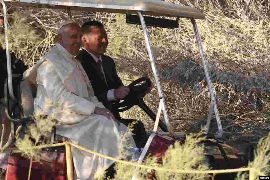 Pope Francis and King Abdullah travel in a golf cart during their visit to the site at Jordan River where Jesus is believed to have been baptized, May 24, 2014.