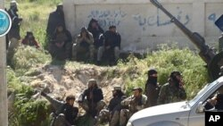 This image posted on the Twitter page of Syria's al-Qaida-linked al-Nusra Front shows fighters from the group in the town of Jisr al-Shughour, Idlib province, Syria, April 25, 2015.