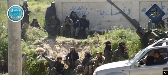 FILE - This image posted on the Twitter page of Nusra Front, April 25, 2015, shows Nusra Front fighters in the town of Jisr al-Shughour, Idlib province, Syria.