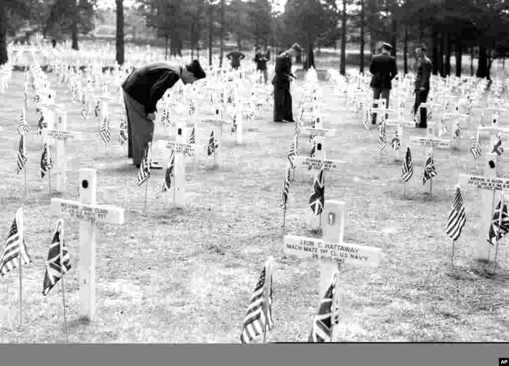 1945年5月30日美国军人在伦敦以南的萨里布鲁克伍德公墓纪念日仪式之后,寻找朋友的坟墓。