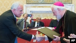 Vatican Foreign Minister Paul Gallagher, right, and his Palestinian counterpart, Riad al-Malki, shake hands after signing a treaty — covering church operations in parts of the Holy Land under Palestinian control — at the Vatican, June 26, 2015.