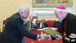 Menteri Luar Negeri Vatikan Paul Gallagher, kanan, dan Menteri Luar Negeri Palestina, Riad al-Malki, berjabat tangan setelah menandatangani perjanjian, tentang operasi gereja di Tanah Suci di bawah pengawasan Palestina, di Vatikan, 26 Juni 2015.