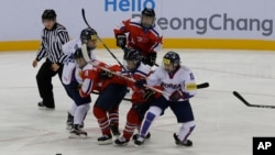 South Korea, wearing white uniforms, and North Korean players compete during their IIHF Ice Hockey Women's World Championship Division II Group A game in Gangneung, South Korea, April 6, 2017.