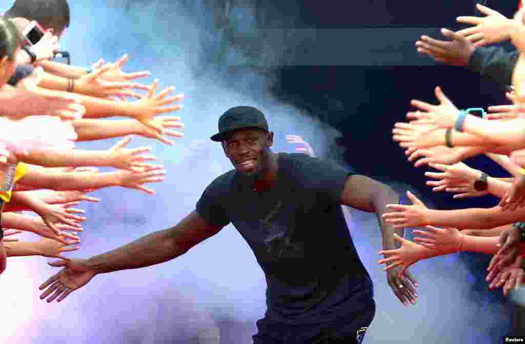 Campeão olimpico jamaicano Usain Bolt cumprimenta fãs durante campeonato de atletismo em Melboune na Austrália.