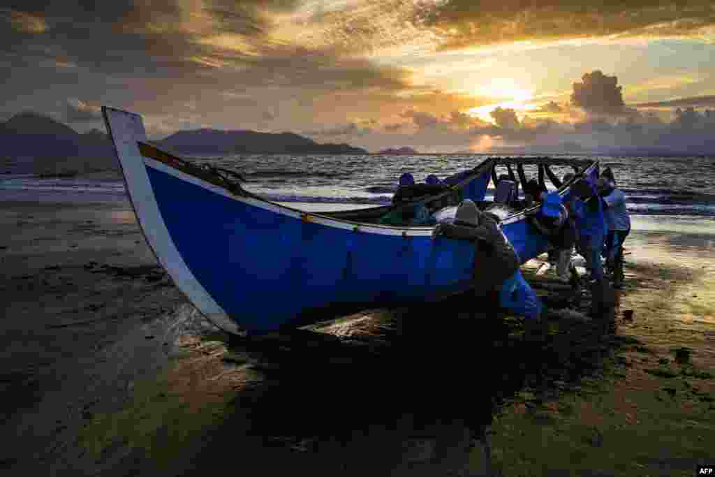 Fishermen push their boat onto the shore upon returning from the sea as the sun sets in Banda Aceh, Indonesia.
