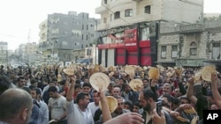 In this citizen journalism image made on a mobile phone, Syrian men carry bread loaves during a protest against Syrian President Bashar Assad's regime, in the coastal town of Banias, Syria, May 3, 2011