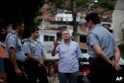 FILE - Rio state Public Safety Director Jose Mariano Beltrame, second right, talks to police officers of Peacemaker Police Unit program, UPP, the during a visit to the Morro dos Macacos slum in Rio de Janeiro, Brazil, Nov. 6, 2010.