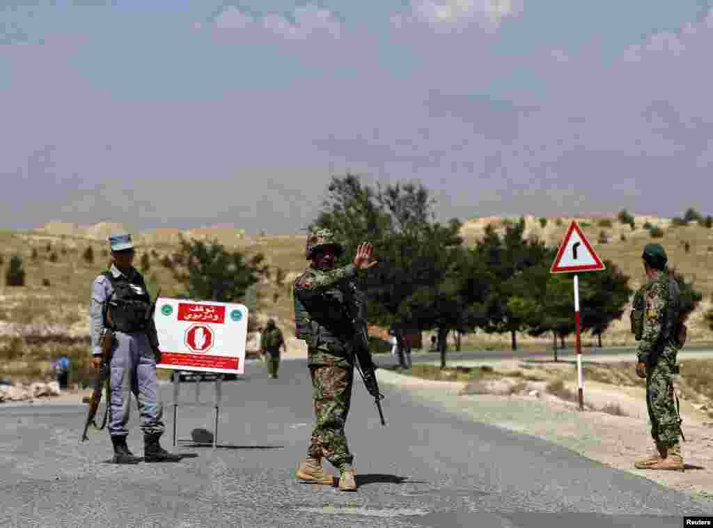 An Afghan National Army (ANA) soldier gestures at vehicles to stop at a check point near the British-run military training academy Camp Qargha, in Kabul, Aug. 6, 2014.