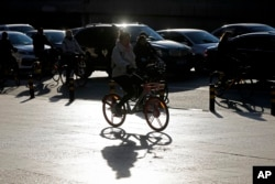 FILE - Commuters ride bicycles past cars clogged with heavy traffic during the morning rush hour in the Central Business District of Beijing, China, Nov. 15, 2017.