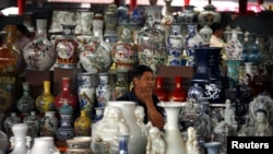 A vendor sits amongst his collection of ceramics as he waits for customers at a small market in central Beijing September 8, 2012. China's annual rate of consumer inflation ticked up t o 2.0 percent in August from July's 30-month low of 1.8 percent, offic