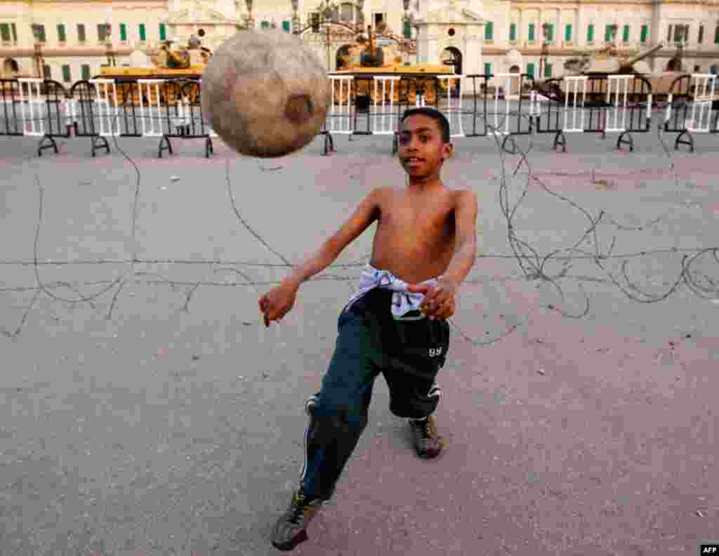 A boy plays soccer in front of army tanks at Abdeen Palace Museum in Cairo on Thursday. (Reuters/Amr Abdallah Dalsh)