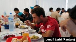 Warga Aljazair berbuka puasa di pusat distribusi makanan amal oleh asosiasi kemanusiaan Ihcene di pinggiran Algiers 30 Juli 2013. Ihcene meluncurkan pusat distribusi makanan amal selama Ramadan, bulan paling suci dalam kalender Islam. (Foto: REUTERS /Loua