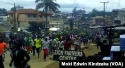 Hundreds of youths run through the streets of Ekona, cheering, waving palm fronds, and holding signs demanding independence in this image taken from video, Sept. 22, 2017.