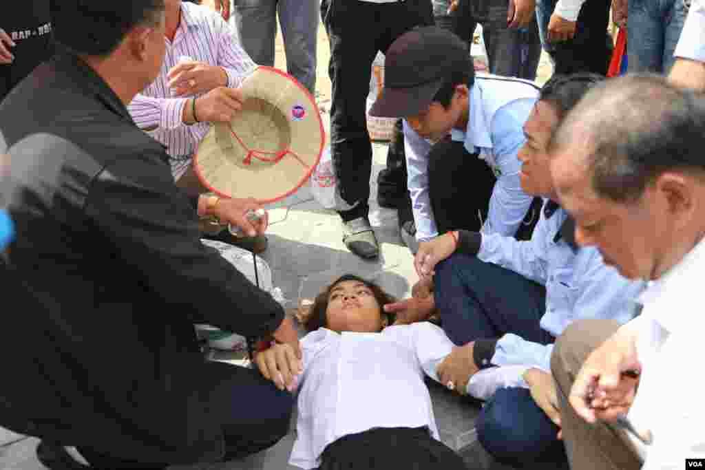 A young female protester who passed out due to heat was helped by fellow protesters, Phnom Penh, Oct. 25, 2013. (Heng Reaksmey/VOA Khmer)