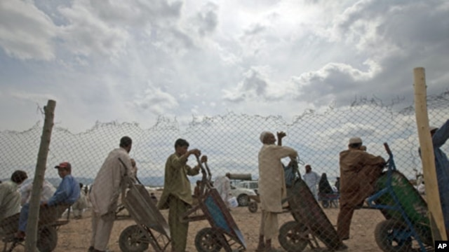 Men line up with their wheelbarrows to transport supplies for families displaced by military operations last year against militants in Bara, at the United Nations High Commission for Refugees-supported Jalozai camp in Pakistan's northwest, April 11, 2012.