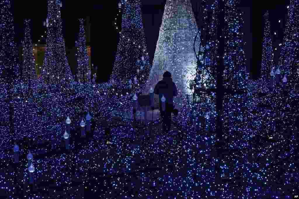 Seorang staf memeriksa instalasi cahaya di distrik Shiodome, Tokyo, Jepang.