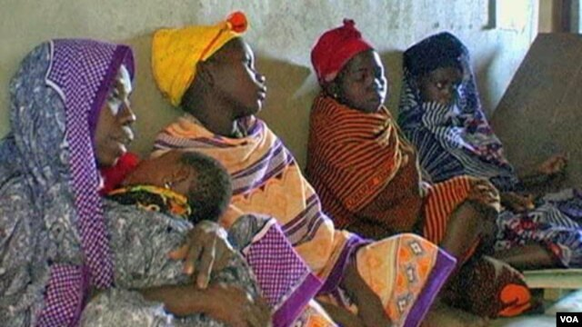 FILE - African women waiting for medical care.