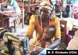 A seamstress trainee works on a sewing machine with a child on her lap.