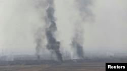 De la fumée s'échappe à Bartila, à l'est de Mossoul lors des combats contre le groupe État islamique, Irak, le 18 octobre 2016.